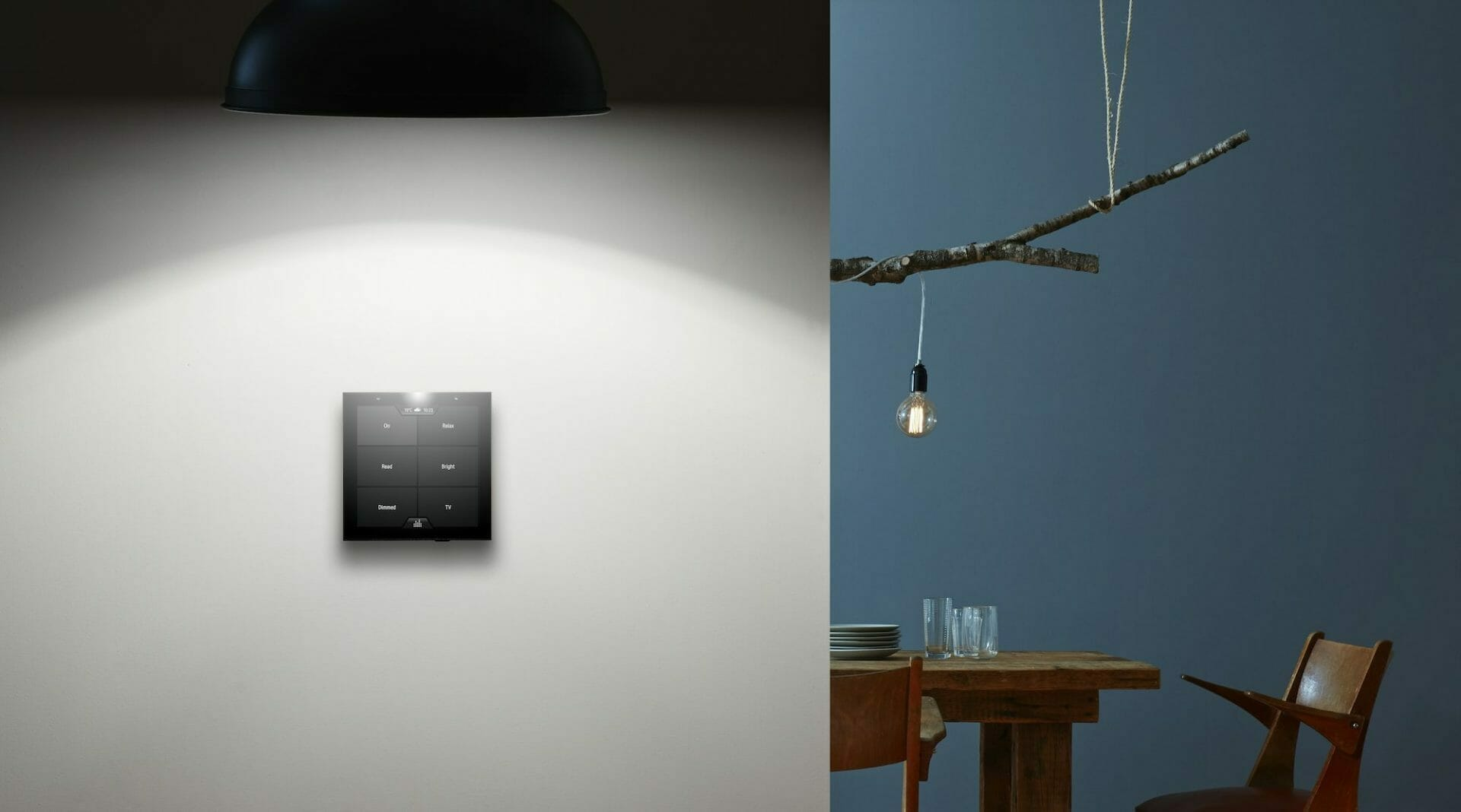 Violet's SmartSwitch Lite wall mounted with a lamp above it and a dining table in the background