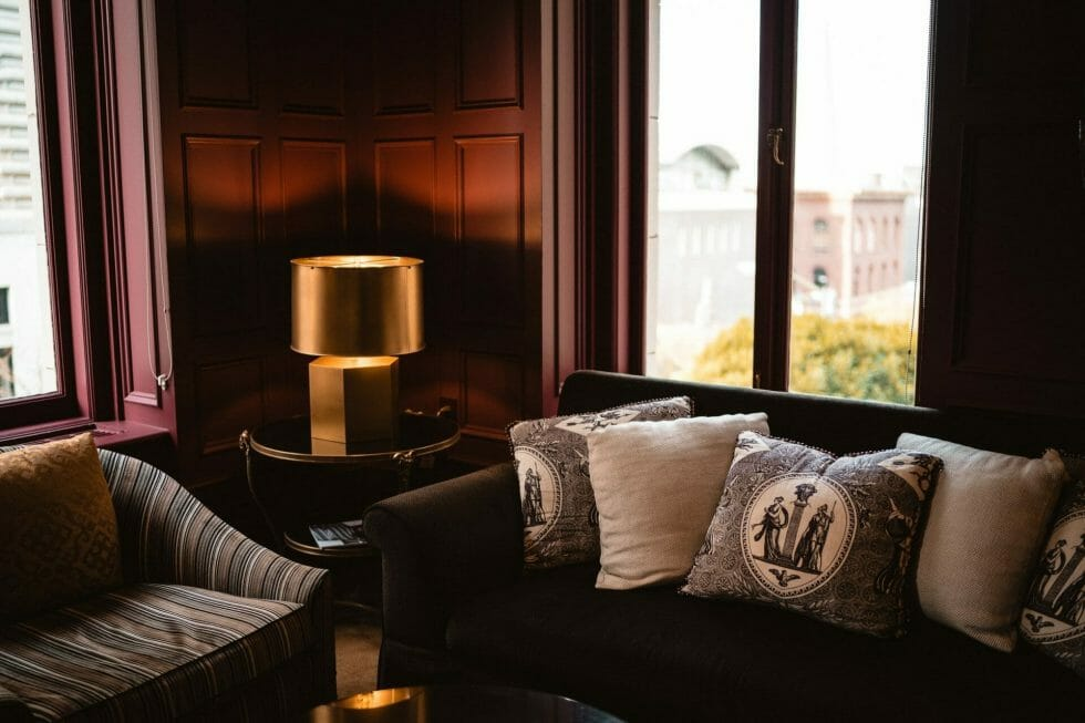 Stylish living room with leather sofas with detailed cushions and a gold table-mounted lamp as the focus
